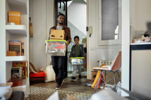 Afro-Caribbean single father in late 20s and 7 year old son smiling as they carry cardboard boxes and plastic containers into new home.