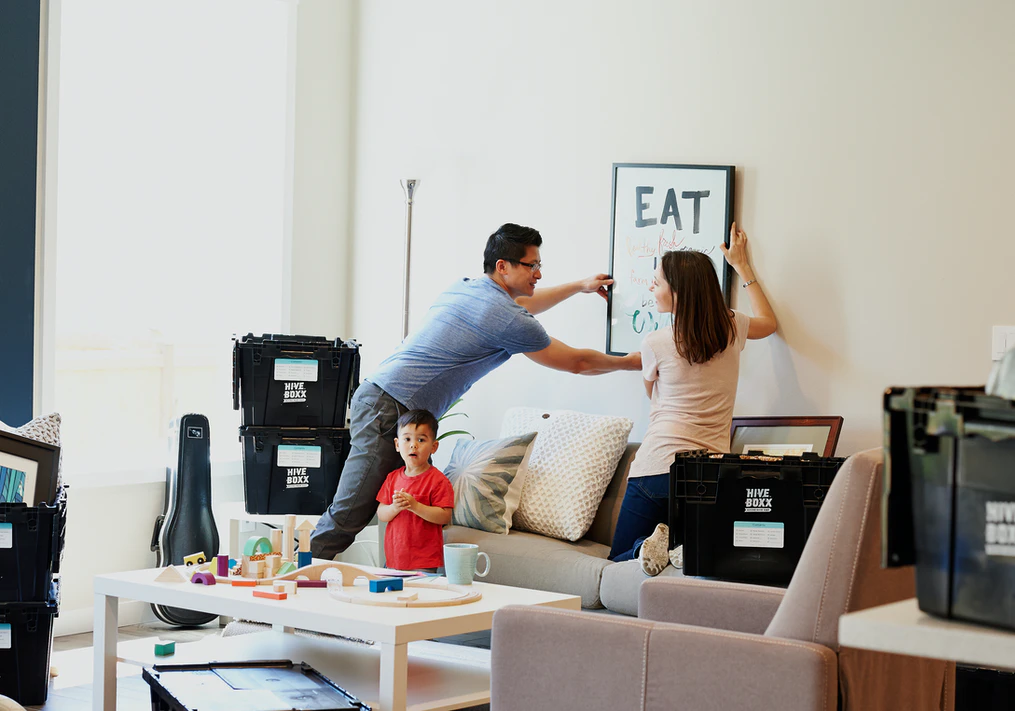 A Couple Hangs a Picture on the Wall While Surrounded by Moving Boxes and with their Son Standing Nearby