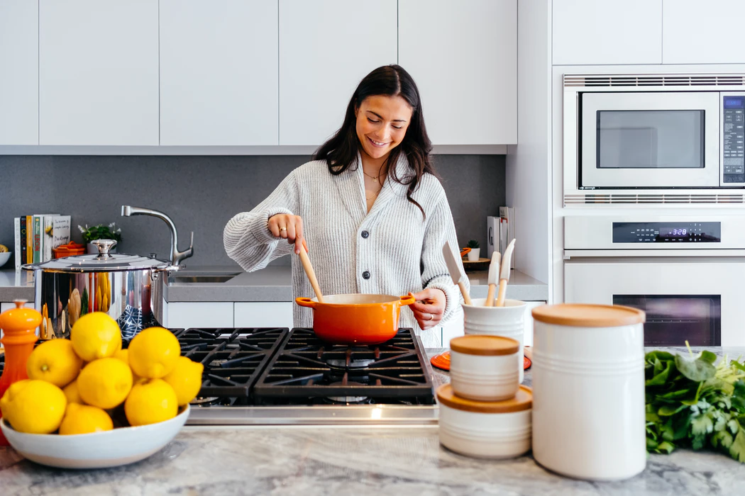 A Woman in a Cream Sweater Stands at the Stove and Stirs Something in an Orange Pot