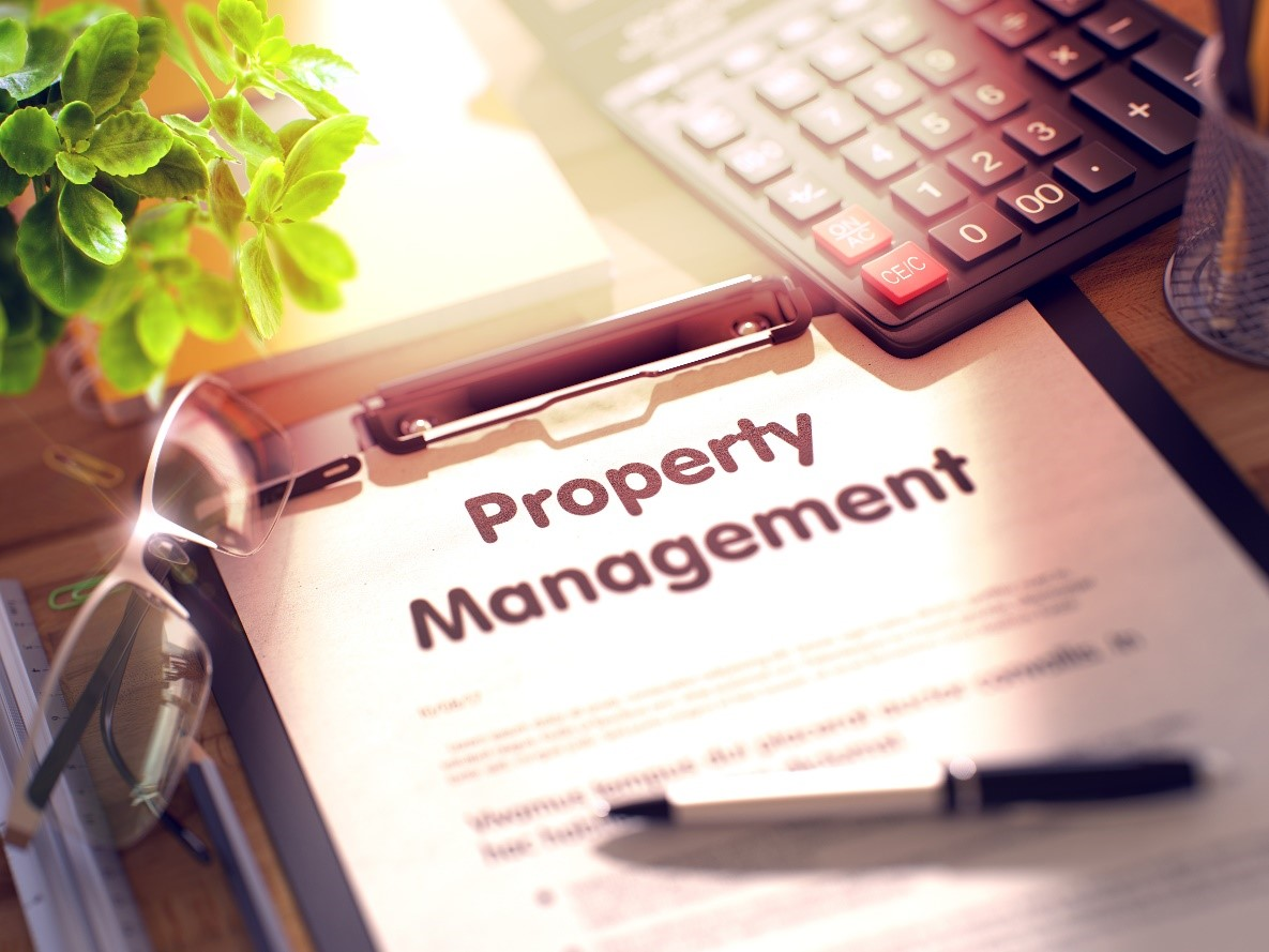 """A picture of a clipboard with bold words reading """"Property Management"""" and a pen, glasses, and calculator on the desk."""