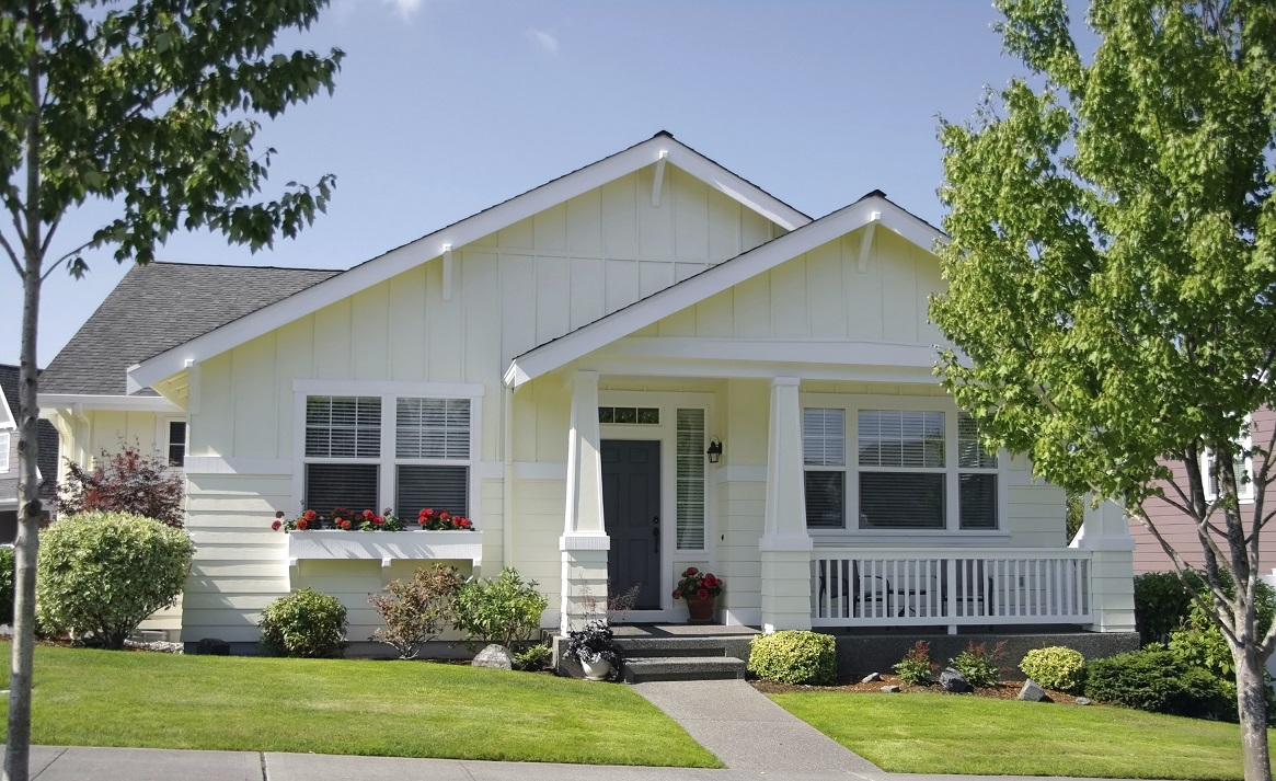 White, well-maintained house with beautiful landscaping