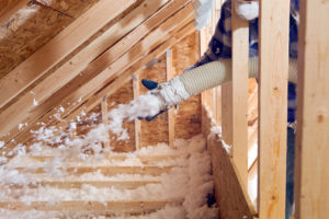 Spraying Blow-In Fiberglass Insulation Between the Attic Trusses of Your Warren Rental Home
