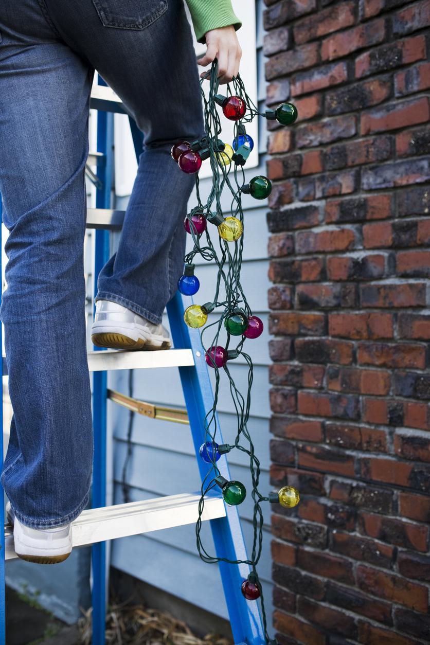 Royal Oak Tenant Hanging Christmas Lights for the Holiday Season