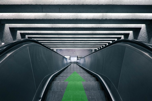Escalator with a Green Arrow Pointing Down