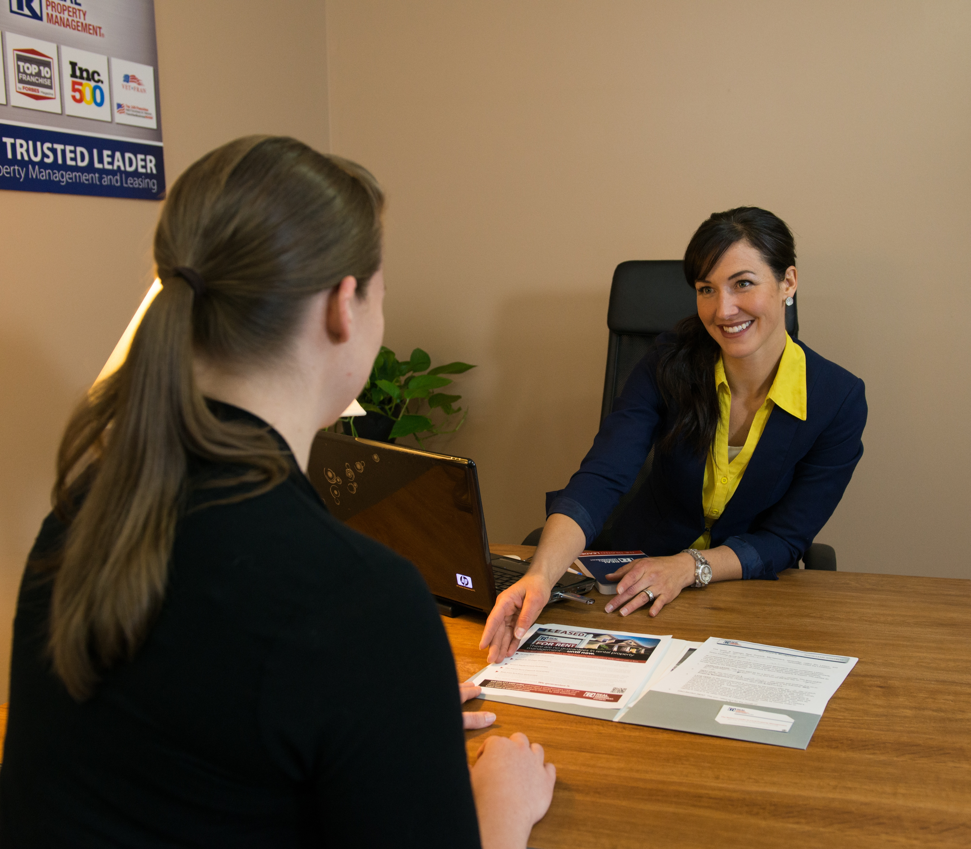 A Potential Resident Sitting at a Desk with a Real Property Management East San Gabriel Valley Manager