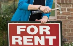 """Someone putting a """"For Rent"""" sign in a front yard"""