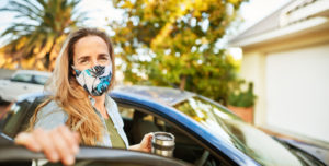 A woman in a face mask getting out of a car in the driveway of a rental property
