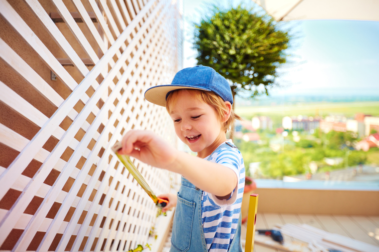 Young Exeter Resident Measuring the Trellis on an Outdoor Patio