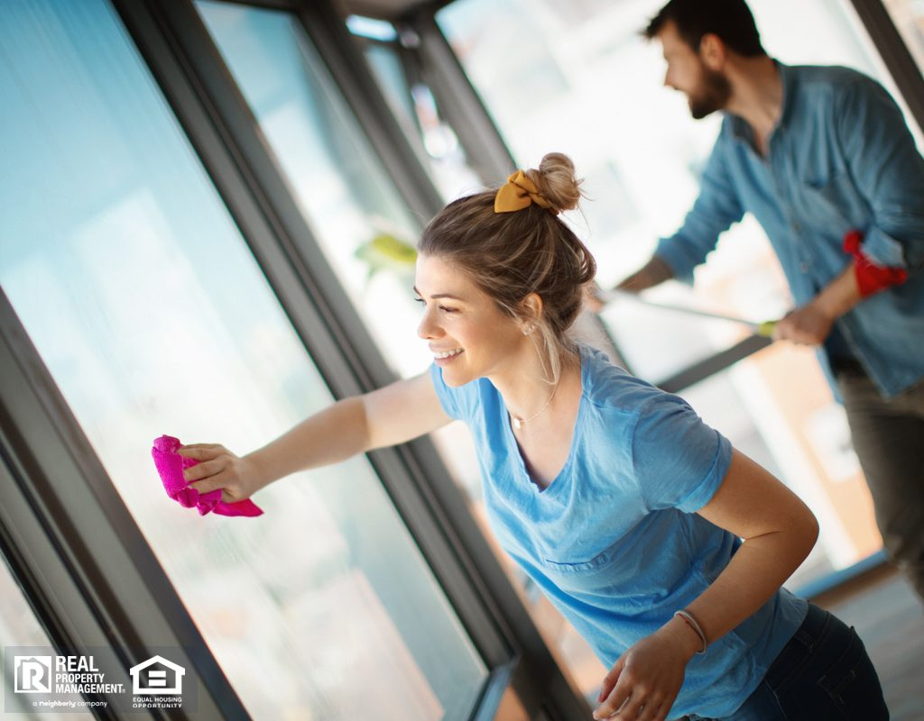 Couple Deep Cleaning Windows in Apartment