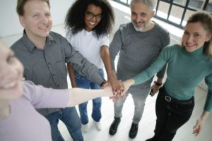 A group of adults in a semi-circle putting their hands together
