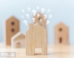Questions Marks Hovering Above a Wooden Block in the Shape of a House