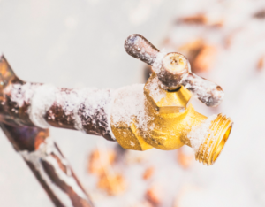 Frozen Outdoor Water Faucet and Pipes Covered in Snowflakes