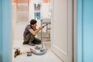 Humble Landlord Fixing a Sink in the Bathroom